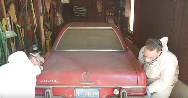 two men approaching a red mercedes with masks on in a garage