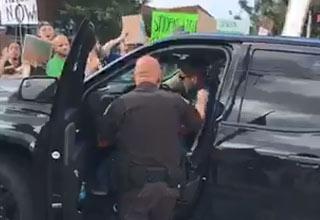 a cop scolding a man driving a black truck