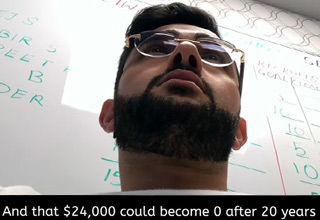 a man with glasses and a beard sitting in front of a whiteboard
