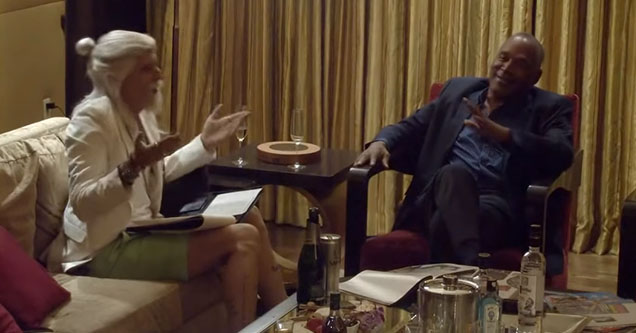 a guru looking man and a second man in a suit having conversation