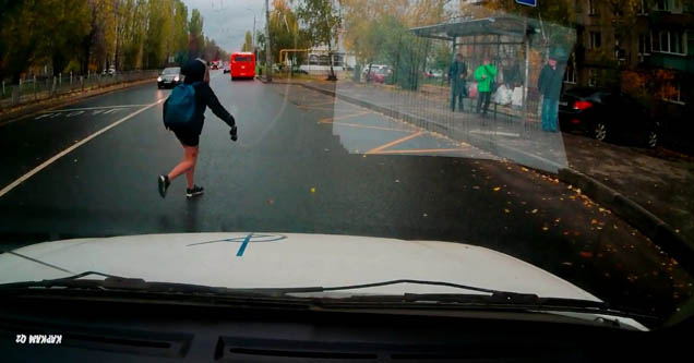 a woman running into the street as captured by a dash cam