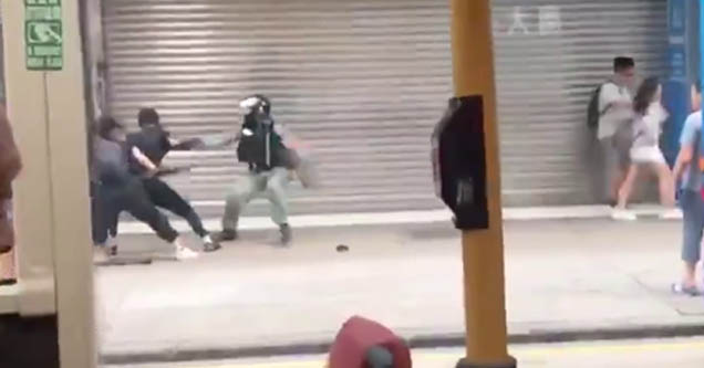 a hong kong man preparing to jump to kick a riot officer