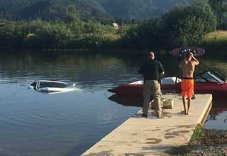 A photo of a car that fell into a lake dragging a boat.