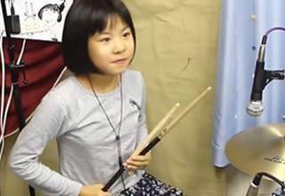 a young Asian girl playing the drums