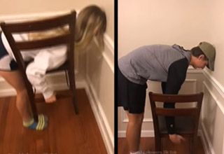 a girl and a boy bending over to pick up the chair