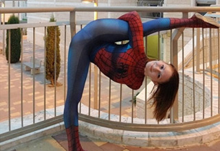 a woman in spider man cosplay doing a split
