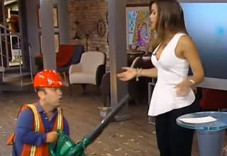 a little person with a leaf blower and an news anchor