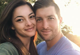 Tim Tebow and his wife Demi Nel-Peters smiling with the sun setting behind them