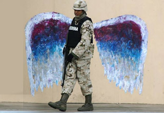 a soldier in front of angel wings painted on a wall