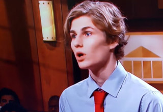 a kid in a blue shirt and red tie on judge judy
