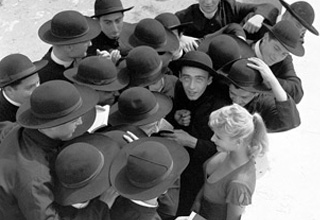 a group of rabbis around a blonde woman in a black and white picture