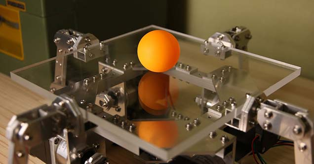An orange ping pong ball sitting on top of an arduino powered device that perfectly bounces the ball.