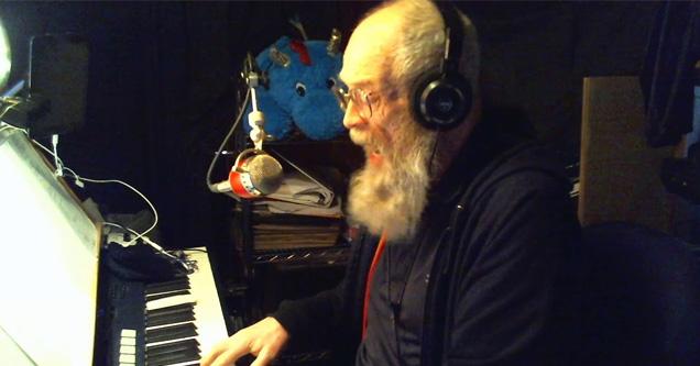 an older man playing keyboard and singing   song about coronavirus