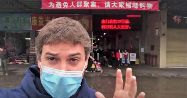 American in China gives straightforward tour of wet markets | pic of a man wearing a face mask standing in front of a wet market in china
