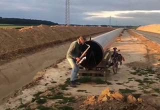 man plays his sax into the opening of a long pipeline