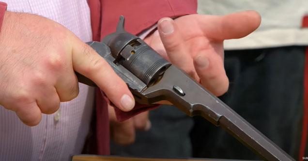 an appraiser holding an old colt revolver