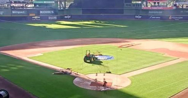 vandal rides on tractor in Miller Park, writes his name in cursive on field