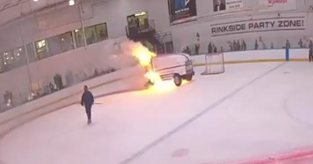 a zamboni on fire driving around the rink