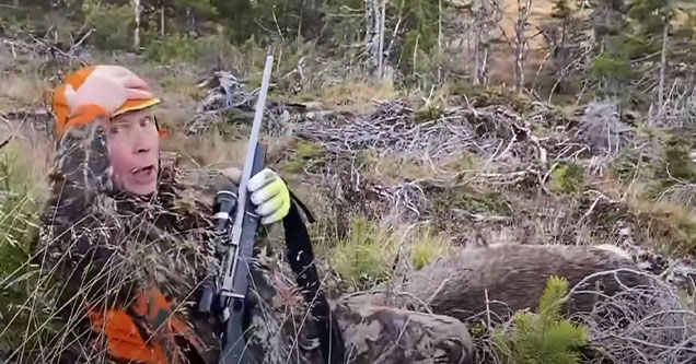 hunter holding a gun and looking into the camera after shooting a charging elk | video of a hunter against an elk