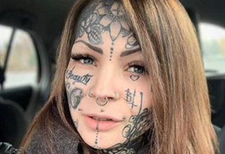 a pretty woman with face tattoos all over