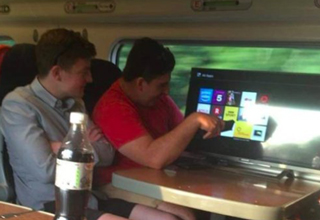 two guys watching a wide screen tv on a train