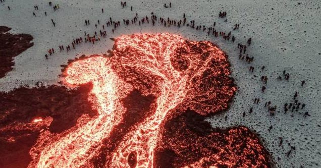 a crowd of people in norway gathered around a huge pool of lava