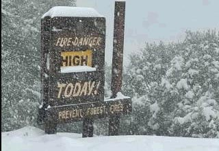 a sign that says high chance of forest fire but its snowing