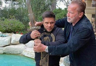 arnold and a boxer holding a huge sword