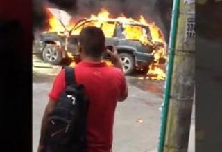 a man in a red shirt watching a car burn