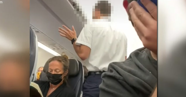 flight attendants on a plane subduing a passenger