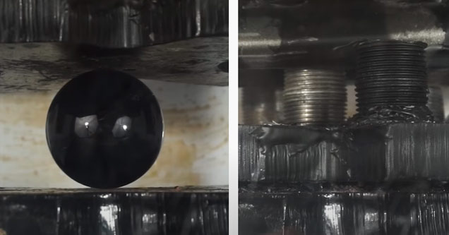 a ball of obsidian being crushed in a hydraulic press