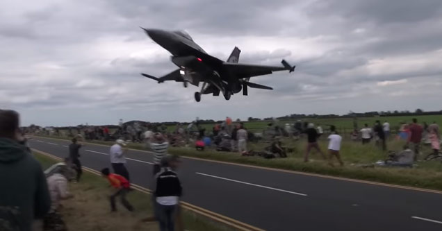 a fighter jet flying very low over crowd