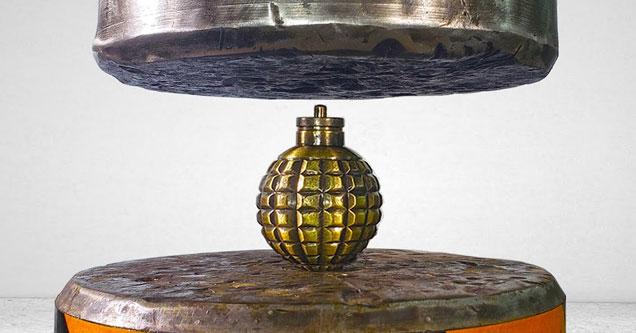 a hydraulic press crushing a grenade