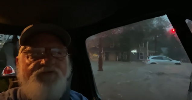 old man in a truck stuck in flood waters