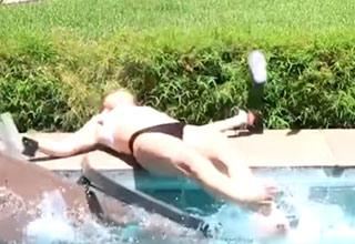 a girl in a bikini who slipped and fell onto her back by the edge of the pool