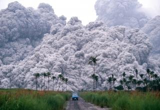 a photo of volcanic ash and a tiny blue truck fleeing from it