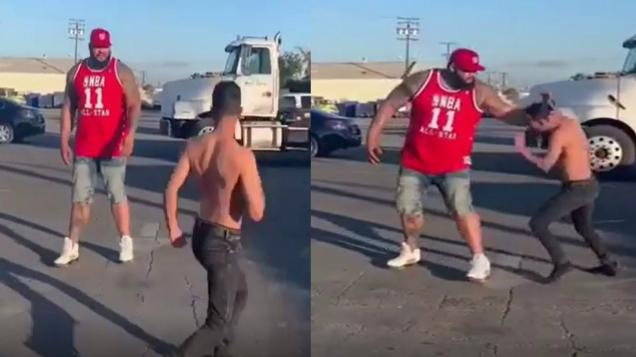 a photo of two people fighting one is short and the other is very large