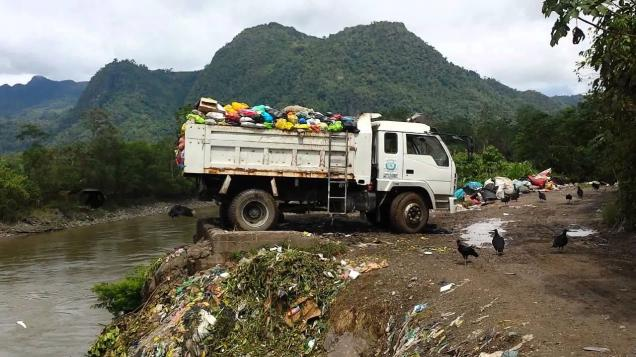 truck carrying trash backing toward a river