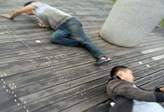 A company in China forced employees to crawl on their hands and knees around a local lake.