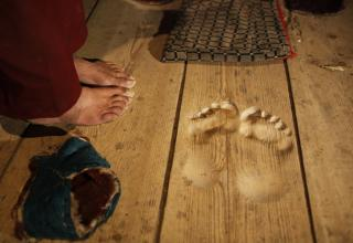 a photo of a wood floor with depressions of a mans feet who stood there to pray for 20 years