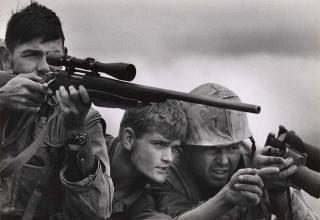 A U.S. Marine sniper team in Vietnam. February, 1968. A man looks down the scope of his rifle while two others look on, point, and discuss.