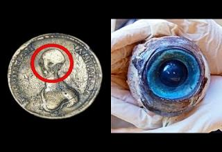 a photo of a gold coin with an alien head and a blue marble inside a rock