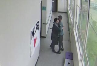a high school coach hugging a student with a gun